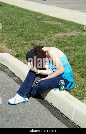 Betrunkene Teenager weiblich liegt am Rande der Straße Bordstein nach zu viel Alkohol - Stockfoto