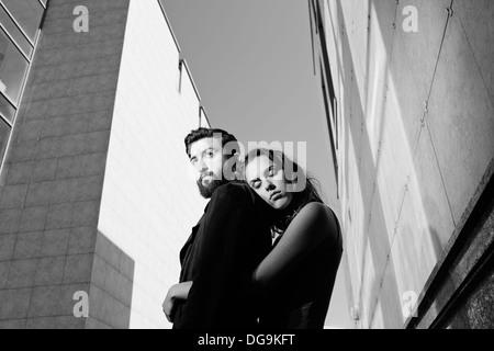 Porträt der ruhige Mann umarmt von seiner Freundin auf Grund moderner Gebäude - Stockfoto