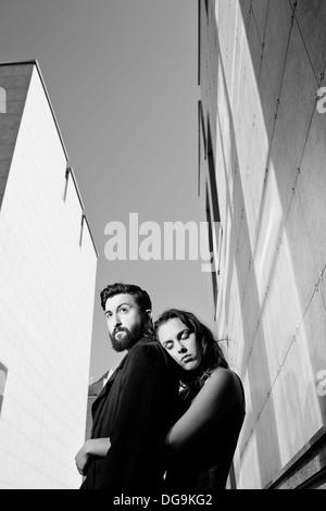 Schwarz-weiß-Bild der ruhige Mann umarmt von seiner Freundin auf Grund moderner Gebäude - Stockfoto