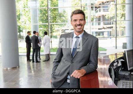 Geschäftsmann gelehnt Rezeption lächelnd allgemein - Stockfoto