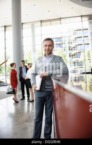 Geschäftsmann hält Laptop gelehnt Rezeption - Stockfoto