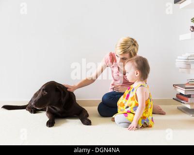 Mutter mit Tochter (12-17 Monate) spielen mit Hund - Stockfoto