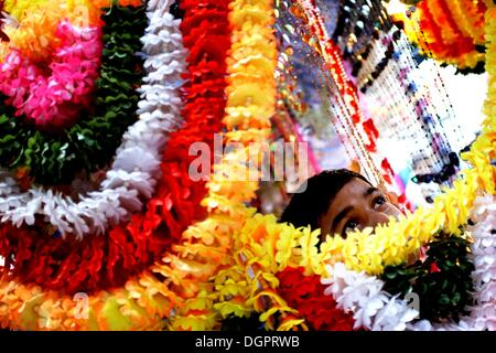 Kuala Lumpur, Malaysia. 23. Oktober 2013. Ein Kind Herumspielen Diwali Kunststoff Blume für die Dekoration am Jalan - Stockfoto