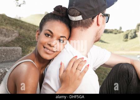 Junge Frau umarmt Freund - Stockfoto