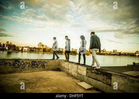 Vier Freunde, die zu Fuß entlang der Betonmauer, Russland - Stockfoto