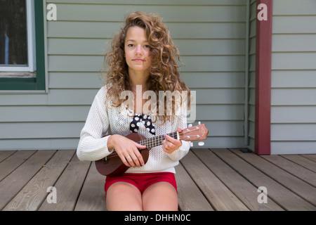 Teenager-Mädchen sitzen auf der Veranda halten Miniatur Gitarre - Stockfoto