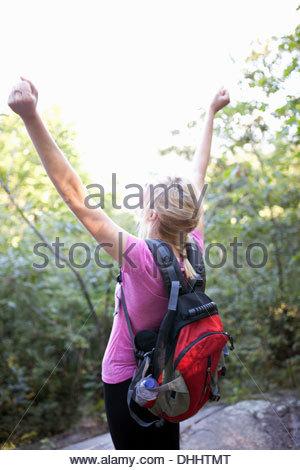 Rückansicht der Frau im Wald mit Armen aufstehen - Stockfoto