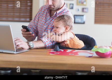 Mann mit Baby saß am Küchentisch arbeitet - Stockfoto