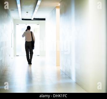 Geschäftsmann, den Korridor hinunter, am Telefon - Stockfoto
