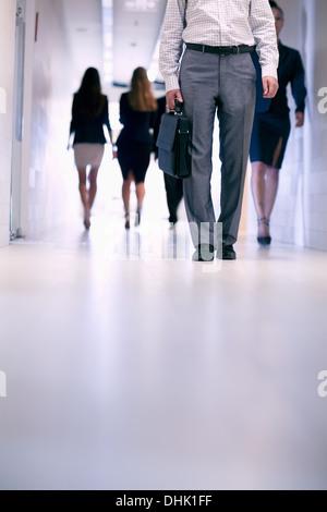 Niedrige Sicht von Menschen zu Fuß durch den Korridor in einem Bürogebäude - Stockfoto
