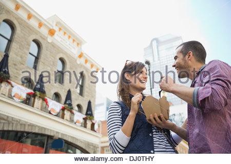 Niedrigen Winkel Blick auf paar Mahlzeit aus Imbisswagen - Stockfoto