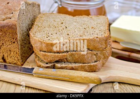 Ein Stapel von Scheiben Roggen-Brot mit einem Messer auf einen Teller, Serviette, Laib Brot, ein Glas Honig, butter - Stockfoto