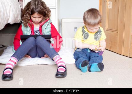 Kinder bei der Nutzung digitaler Tablet und Handy - Stockfoto