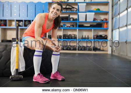 Frau sitzt auf Reifen in Crossfit gym - Stockfoto