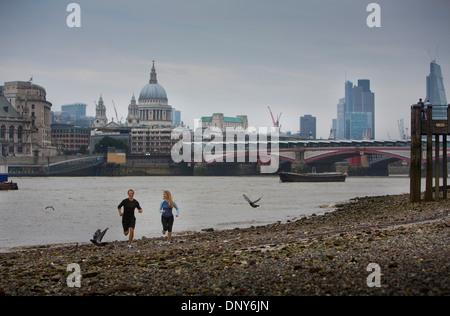 Gary Hicking, Personaltrainer in London, UK, Joggen mit einem Client auf der Themse mit City of London als Kulisse - Stockfoto