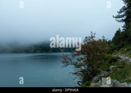 Niedrige Wolken hängen über dem Lac de Gaube im Vallee de Gaube in den französischen Pyrenäen - Stockfoto