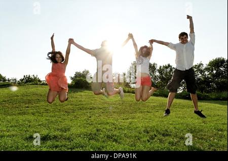 Gruppe junger Erwachsener, die Luft im Bereich springen - Stockfoto