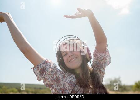 Porträt von Mitte erwachsenen Frau tanzt im Feld tragen von Kopfhörern mit erhobenen Armen - Stockfoto