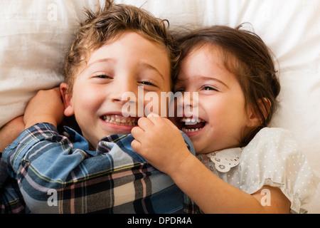 Kinder auf Bett liegend - Stockfoto