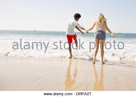 Paar in der Brandung waten - Stockfoto