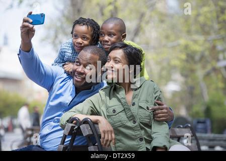 Eine Familie Eltern und zwei jungen, die mit dem Fotografieren mit einem Smartphone - Stockfoto