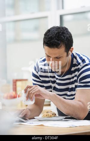 Ein Büro oder Wohnung innen in New York City A Mann in einem gestreiften t-Shirt stützte sich auf die Frühstücks - Stockfoto