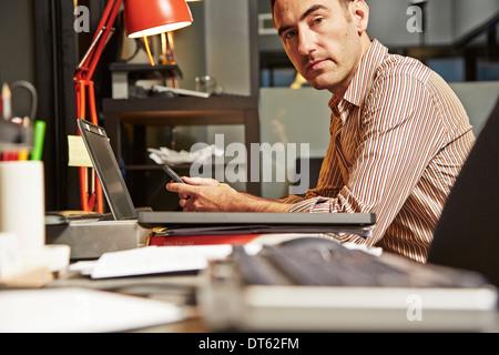 Geschäftsmann am Schreibtisch mit Handy - Stockfoto