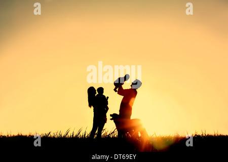 Eine Silhouette einer glücklichen Familie vier Personen, Mutter, Vater, Baby, Kind und ihren Hund vor einem Sonnenuntergang - Stockfoto