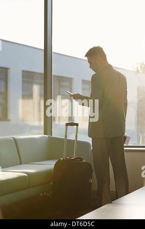 Reifer Mann im Flughafen mit Handy - Stockfoto