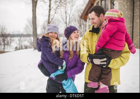 Mutter und Vater tragen Töchter im Schnee - Stockfoto