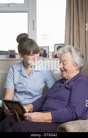 Körperpflege-Assistent mit senior Frau Foto betrachten - Stockfoto
