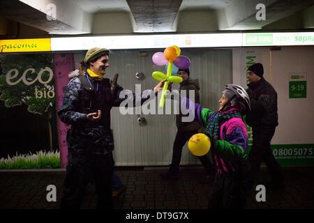Kiew, Ukraine. 9. Februar 2014. Anti-Protestester gekleidet in Armee Anzug spielt mit einem Kind in der Nähe von - Stockfoto