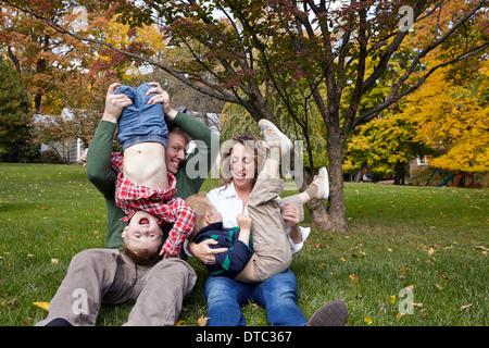 Mitte Erwachsenen Eltern und jungen Söhne spielen im Garten - Stockfoto