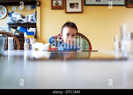 Baby Junge saß am Küchentisch - Stockfoto