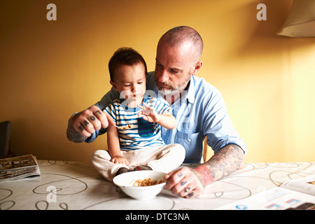 Baby Junge sitzt am Tisch mit Müsli mit Vater - Stockfoto