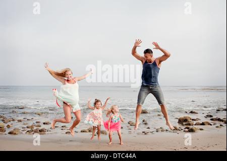 Eltern und zwei junge Mädchen springen Luft am Strand - Stockfoto