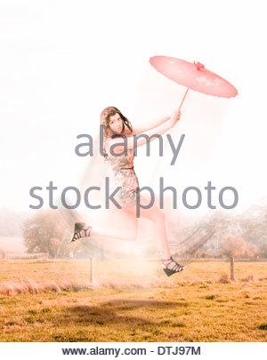 Schöne attraktive Brünette Frau hält ein Dach In ein springen, laufen und springen Bewegung während weg von durchgeführt - Stockfoto