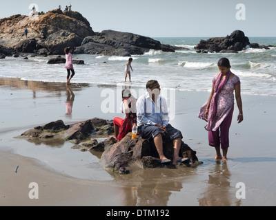 Indien, Goa, Vagator Strand, indische Touristen Sittng auf Felsen am Meeresufer - Stockfoto