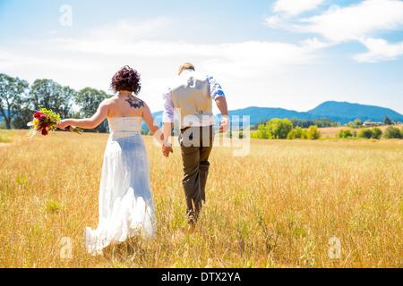 Braut und Bräutigam am Tag ihrer Hochzeit durch ein Feld in Oregon zusammen spazieren. - Stockfoto