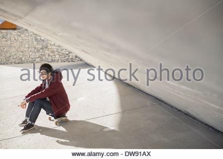Junger Mann sitzt auf Skateboard unter Stadtbrücke - Stockfoto