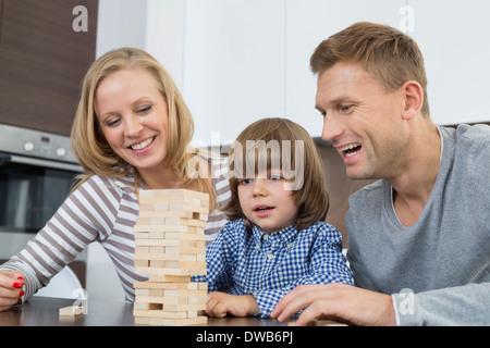 Glückliche Eltern und Sohn spielt mit Holzblöcken zu Hause - Stockfoto