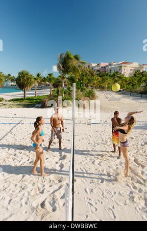 Vier junge Erwachsene Freunde spielen Beach-Volleyball, Providenciales, Turks-und Caicosinseln, Caribbean - Stockfoto