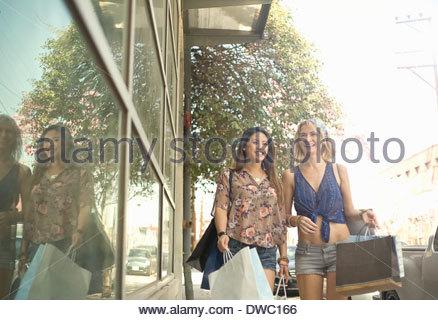 Zwei junge Frauen auf Straße mit Einkaufstaschen - Stockfoto