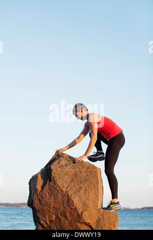 Gesamte Länge der sportlichen Frau Klettern auf Felsen gegen klaren Himmel - Stockfoto