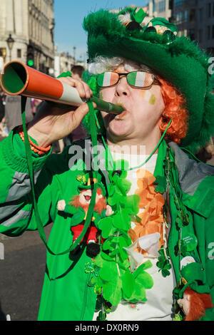 Eine Frau, gekleidet in irischen Farben feiert am St. Patricks Day in London - Stockfoto