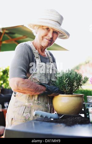 Glücklich senior Frau pflanzt neue Anlage in Terrakotta-Topf auf einen Zähler im Hinterhof. Ältere weibliche Gärtner - Stockfoto