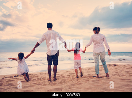 Glückliche junge Familie, die Spaß am Strand bei Sonnenuntergang - Stockfoto