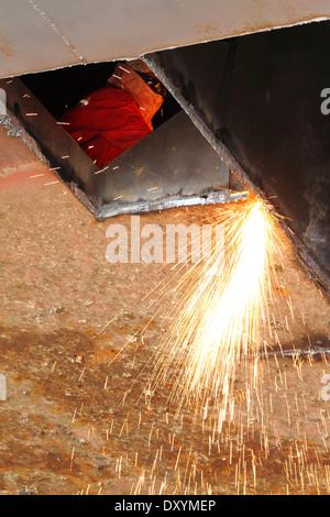 Funken fliegen als Stahl, aus einem alten Lastkahn durch eine Sauerstoff Acetylen-Taschenlampe auf einer Werft in - Stockfoto