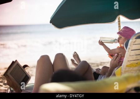 Familie auf Liegestühlen liegen, lesen und einen Drink - Stockfoto