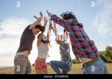 Vier Freunde springen mit erhobenen Armen - Stockfoto